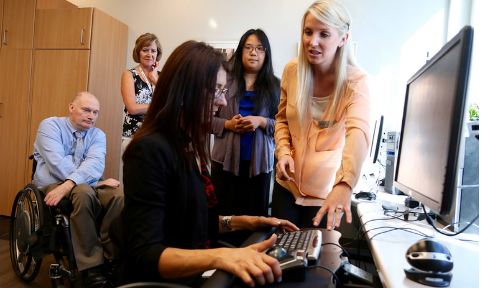 Lady in a wheel chair sitting at a computer and looking at the keyboard. There is a women assisting her.
